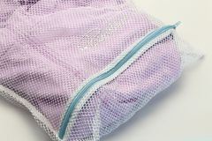 Nets laundry bag, for washing clothes in washing machine on white background. Stock Photos