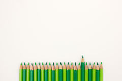 Ordered group of bright green pencils on white background with one pen standing out Stock Images