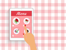 Ordering food in restaurant. Female hand is ordering food in the restaurant via mobile app displayed on tablet pc Stock Photo