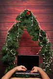 Ordering gift on christmas. Via typing on laptop. Wooden tree new year background Royalty Free Stock Photo
