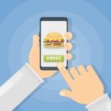 Ordering hamburger through phone. Ordering hamburger through smartphone. Hands holding device Royalty Free Stock Images
