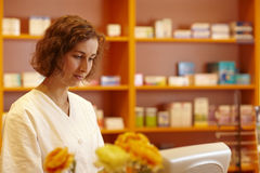 Ordering over the internet. Pharmacist typing on computer behind pharmacy counter Royalty Free Stock Photos