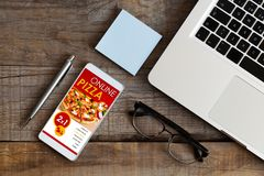 Ordering pizza by mobile at work. Royalty Free Stock Photo