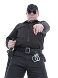 Ordering policeman. Policeman wearing black uniform and glasses pointing in ordering manner Stock Photo