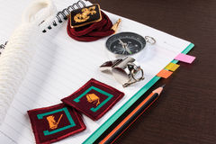 Orderliness white scout rope, compass, scouts badge and pencil o. N wooden table. A close up view Royalty Free Stock Images