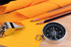 Orderliness white scout rope, scarf, whistle, compass, pencil and paper note. Stock Photos
