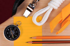 Orderliness white scout rope, scarf, whistle, compass, pencil and paper note. Royalty Free Stock Photo