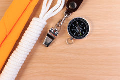 Orderliness white scout rope, scarf, whistle and compass. Orderliness white scout rope, scarf, whistle and compass on wooden table Royalty Free Stock Images