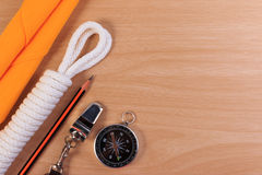 Orderliness white scout rope, scarf, whistle, pencil and compass. Orderliness white scout rope, scarf, whistle, pencil and compass on wooden table Royalty Free Stock Images