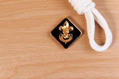 Orderliness white scout rope with vintage boy scouts badge on wooden table. Royalty Free Stock Photography