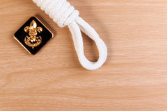 Orderliness white scout rope with vintage boy scouts badge on wooden table. A close up view Royalty Free Stock Images