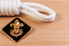 Orderliness white scout rope with vintage boy scouts badge on wooden table. Royalty Free Stock Photos