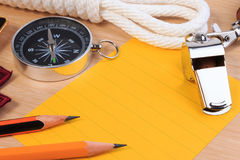 Orderliness white scout rope, whistle, compass, pencil and paper note. Orderliness white scout rope, whistle, compass, pencil and paper note on wooden table Stock Photos