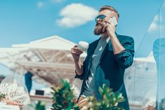Orderly male talking on phone during rest. Low angle portrait of calm bearded man telling on mobile while drinking cup of coffee outside. He wearing contemporary Stock Images