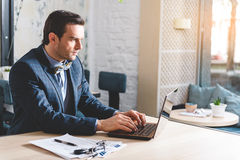 Orderly male working at laptop. Side view composed bristled businessman typing on keypad of notebook computer while sitting at table in apartment Royalty Free Stock Photos