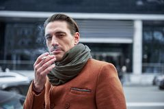 Orderly man smoking cigarette on street royalty free stock photo