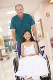 An Orderly Pushing A Little Girl In A Wheelchair Stock Photo