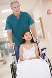 An Orderly Pushing A Little Girl In A Wheelchair Stock Image