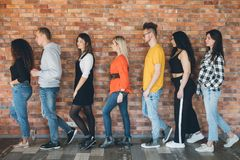 Orderly queue millennials anticipation hope belief. Orderly queue. Millennials moving toward future. Young men women standing in line full length. Anticipation royalty free stock image