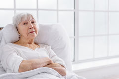 Orderly retiree keeping to bed in clinic Royalty Free Stock Photo