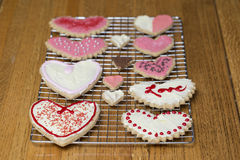 Orderly Valentine's Day heart cookies on a cooling rack set on a royalty free stock image