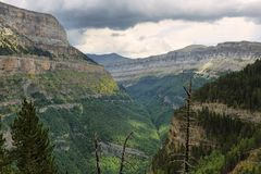 Ordesa canyon in Spanish Pyrenees. Wide view of the huge Ordesa canyon in Spanish Pyrenees. Majestic, deep mountain valley surrounded by vertical, orange walls stock image