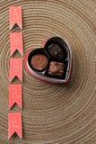 Ordet 'älskar' och en ask av choklader Royaltyfri Foto