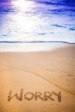 Ordet BEKYMMER som är skriftligt i sanden Royaltyfri Bild