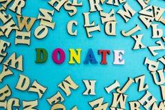 Ordet 'donerar 'läggas ut från mångfärgade bokstäver på en blå bakgrund arkivfoton