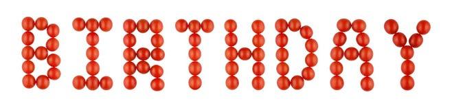 Ordet FÖDELSEDAG som göras från röda tomater på den vita bakgrunden Arkivbilder