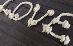Ordet: FÖRÄLSKELSE med repet lägger på träbakgrund Arkivbild