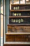 Ordet FÖRÄLSKELSE som är skriftlig med tappning som skrivar ut över den gamla wood trappan Arkivbild