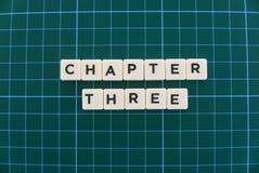 Ordet för kapitel tre gjorde av fyrkantigt bokstavsord på grön fyrkantig matt bakgrund arkivfoton