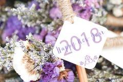 Ordet för lyckligt nytt år 2018 på det vita kortet och lilor blommar backgro Arkivfoton