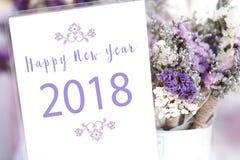 Ordet för lyckligt nytt år 2018 på det vita kortet och lilor blommar backgro Royaltyfri Fotografi
