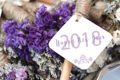Ordet för lyckligt nytt år 2018 på det vita kortet och lilor blommar backgro Royaltyfria Foton