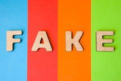 Ordet Fake som komponeras av bokstäver 3D, är i bakgrund av 4 färger: blått rött, apelsin och gräsplan Ord eller begrepp, som kan Arkivbilder