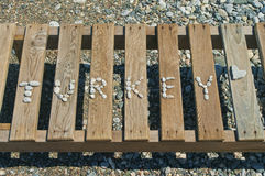 Ordet fodrade med små kiselstenar på sunbed trä Arkivbild