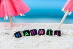 Ordet Hawaii göras av mångfärgade bokstäver på snövit sand mot det blåa havet Royaltyfria Bilder