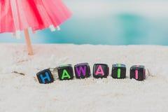 Ordet Hawaii göras av mångfärgade bokstäver på snövit sand mot det blåa havet Arkivfoton