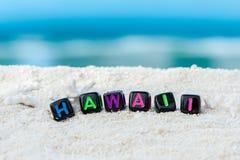 Ordet Hawaii göras av mångfärgade bokstäver på snövit sand mot det blåa havet Royaltyfri Foto
