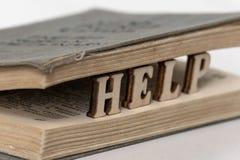 Ordet HJÄLP från träbokstäver mellan sidorna av den gamla Engelsk-ryss ordboken Begreppet av betydelsen av själven-s royaltyfri fotografi
