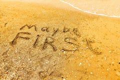 Ordet KANSKE FÖRST som är skriftligt på en sandig strand royaltyfri fotografi