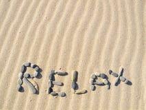 Ordet kopplar av skrivet i sand Arkivfoto