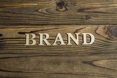 Ordet MÄRKE fodras med bokstäver på en träbakgrund arkivbild