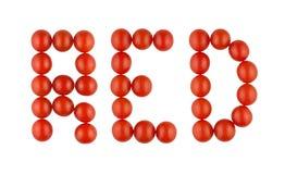 Ordet RÖTT som göras från röda tomater på den vita bakgrunden Royaltyfria Bilder