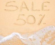 Ordet Sale 50% som är skriftlig i sanden på stranden Arkivfoto