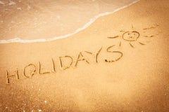Ordet semestrar skriftligt i sanden på en strand Royaltyfri Fotografi