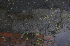 Ordet som är ont på en trottoar i Salem Massachusetts i regnet arkivfoton