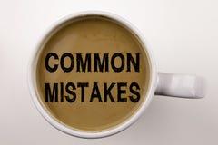 Ordet som skriver gemensamma fel, smsar i kaffe i kopp Affärsidé för gemensamma beslutsfel på vit bakgrund med kopia s Royaltyfri Fotografi